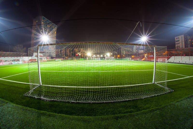 Fotbollarena i upplysta ljusa strålkastare för natt arkivbild