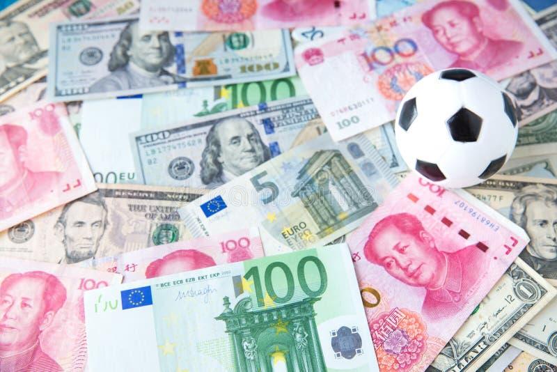 Fotbollboll över mycket pengar korruptionfotbolllek Slå vad och spela begrepp royaltyfri fotografi