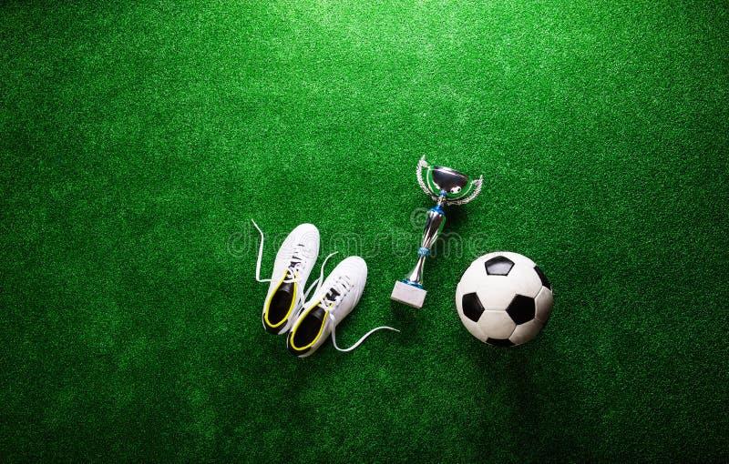 Fotbollboll, dubbar och trofé mot grön konstgjord torva royaltyfri bild