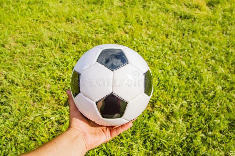 Fotbollboll i hand av fotbollsspelaren på grönt gräs arkivfoto
