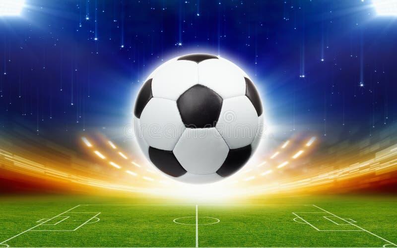 Fotbollboll ovanför grön fotbollsarena på natten arkivbilder