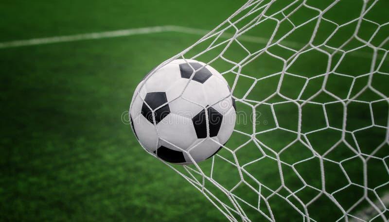 Fotbollboll på mål med netto och grön bakgrund royaltyfri foto