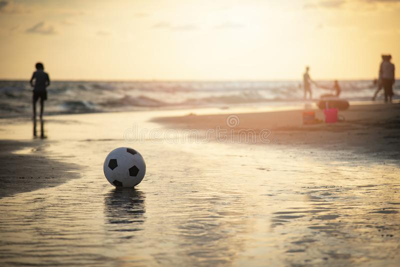 Fotbollboll på sand/spelafotboll på bakgrunden för strandsolnedgånghav fotografering för bildbyråer