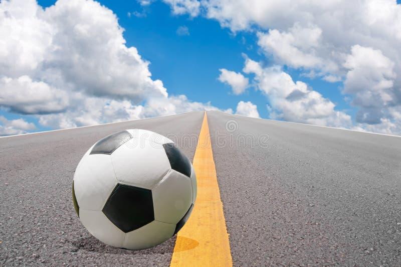 Fotbollboll på vägen fotografering för bildbyråer