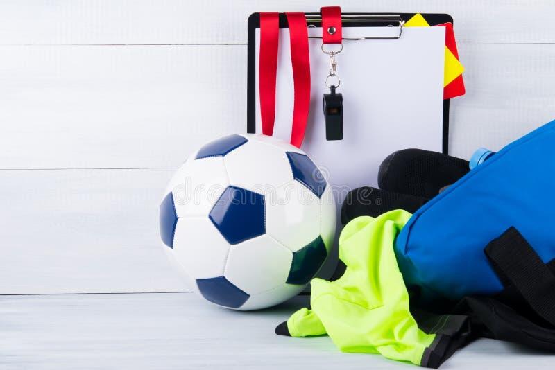 Fotbollboll, vissling, straffkort och en minnestavla för att anteckna en domare och en sportswear i en påse, på en grå bakgrund royaltyfria bilder