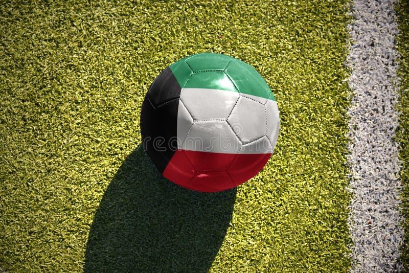 Fotbollbollen med nationsflaggan av Kuwait ligger på fältet royaltyfria foton