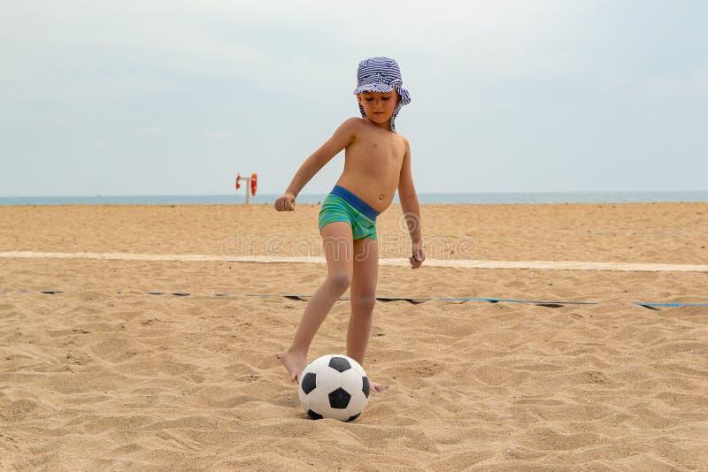 Fotbollen för barnlekar på stranden arkivbilder