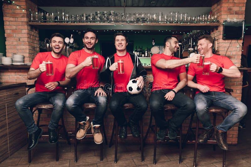 Fotbollfans som håller ögonen på leken dricka öl på sportstången royaltyfri foto
