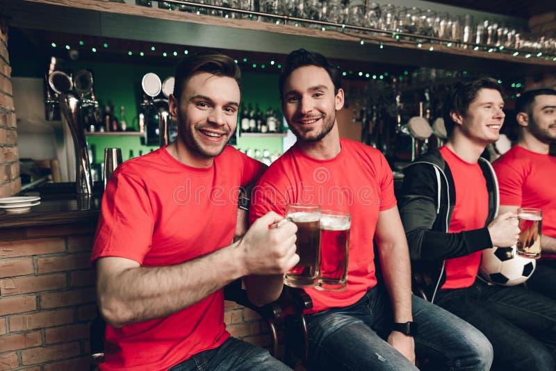 Fotbollfans som håller ögonen på leken dricka öl på sportstången royaltyfria foton