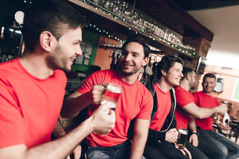 Fotbollfans som håller ögonen på leken dricka öl på sportstången royaltyfri bild