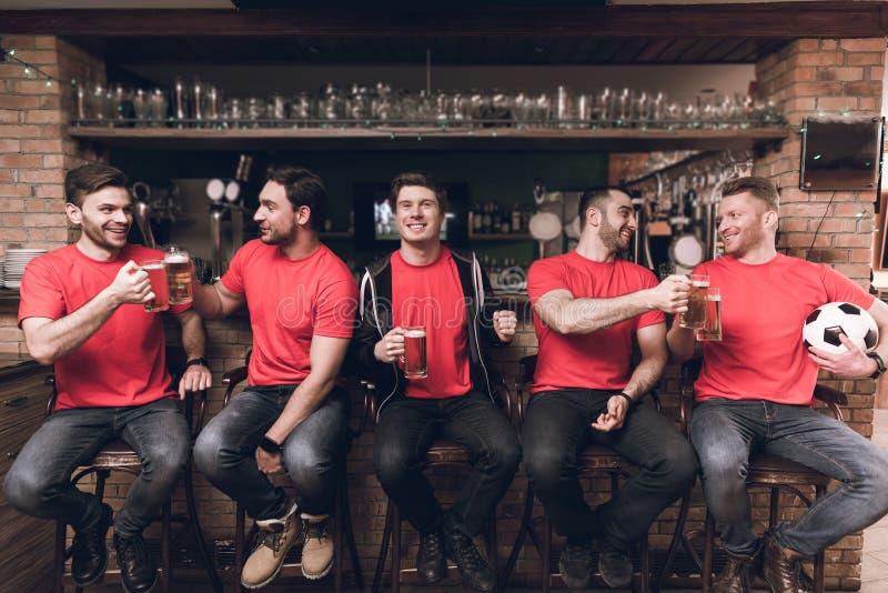 Fotbollfans som håller ögonen på leken dricka öl på sportstången fotografering för bildbyråer