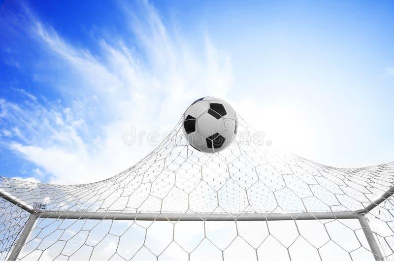 Fotbollfotboll i mål förtjänar arkivfoto