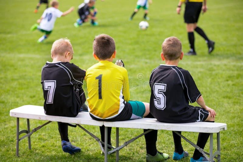 Fotbollfotbollbänk Unga fotbollsspelare som sitter på fotbollersättningbänk royaltyfri fotografi