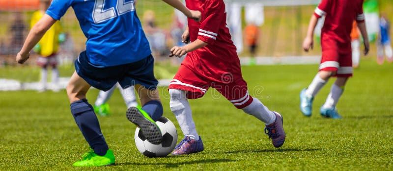 Fotbollfotbollsmatch för barn Pojkar som kör och sparkar Foo arkivfoto