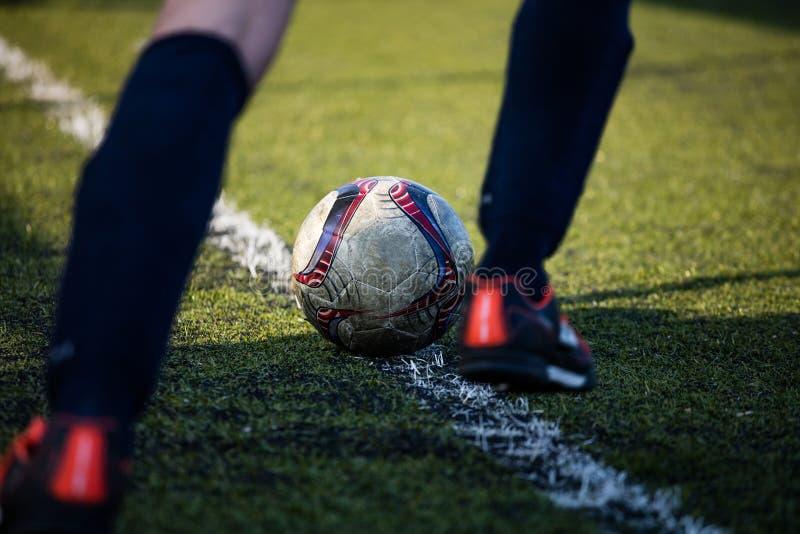 Fotbollfotbollspelare som är klar att sparka fotbollbollen, i grönt fält på en solig dag arkivbild