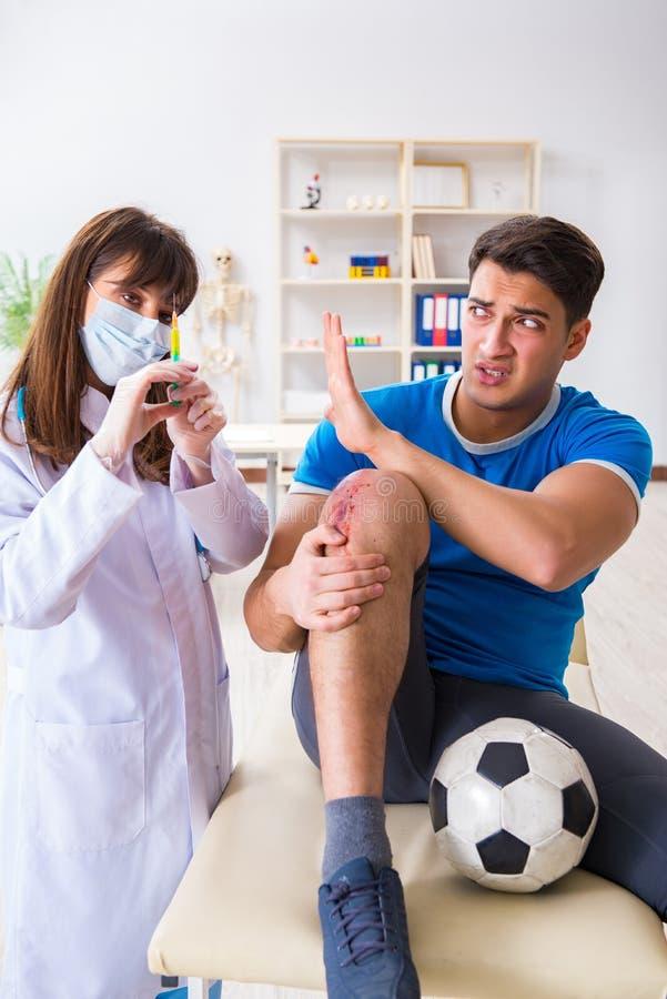 Fotbollfotbollspelaren som besöker doktorn efter skada arkivfoton