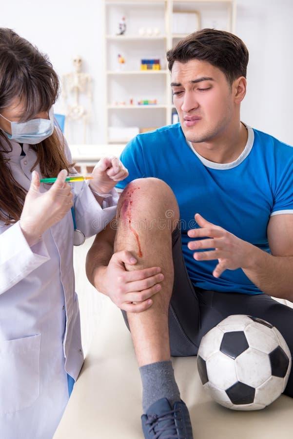 Fotbollfotbollspelaren som besöker doktorn efter skada arkivbilder
