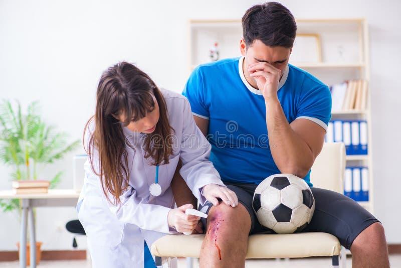 Fotbollfotbollspelaren som besöker doktorn efter skada royaltyfri bild