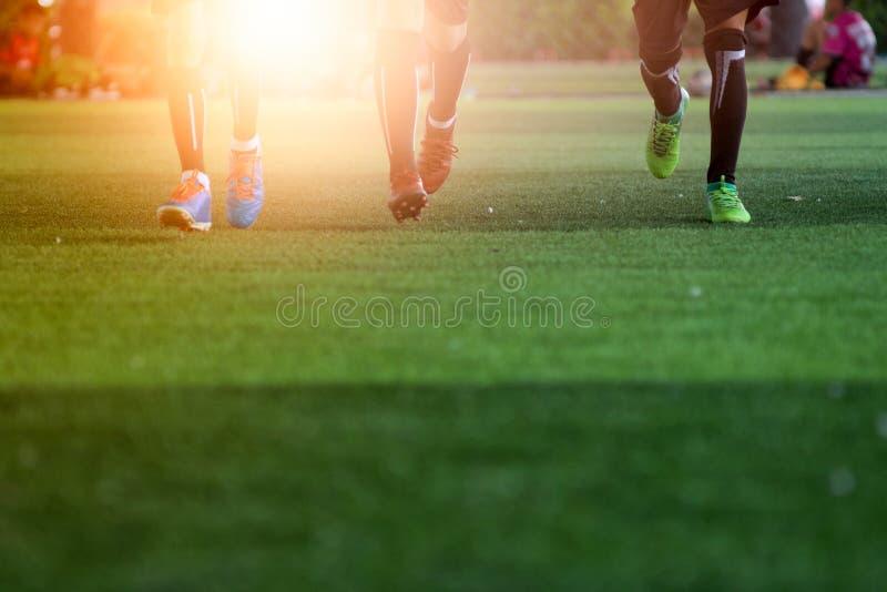 Fotbollfotbollsspelarna på stadion med solnedgång fotografering för bildbyråer