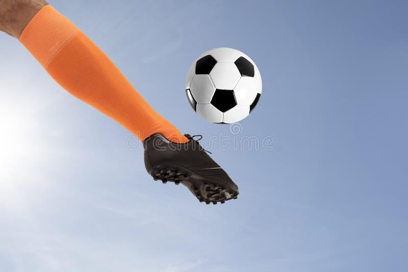 Fotbollfoten som sparkar bollen på himmelbakgrund royaltyfri fotografi