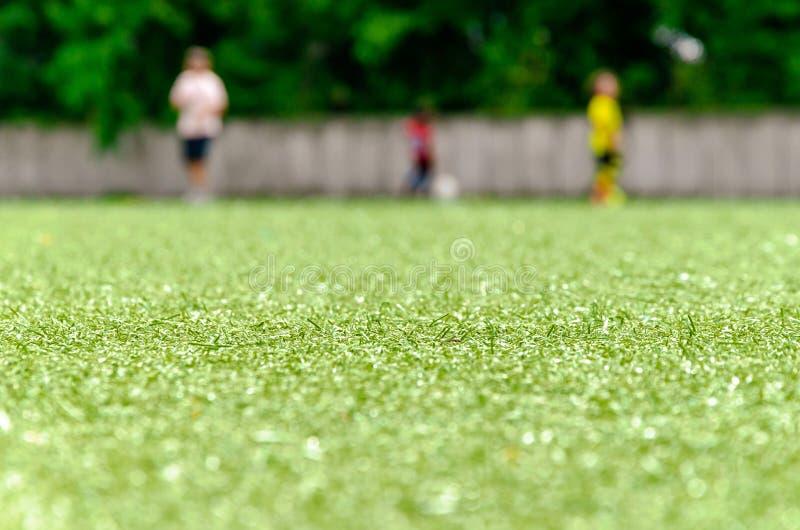Fotbollgräsmatta, spelare tre i bakgrund royaltyfri foto