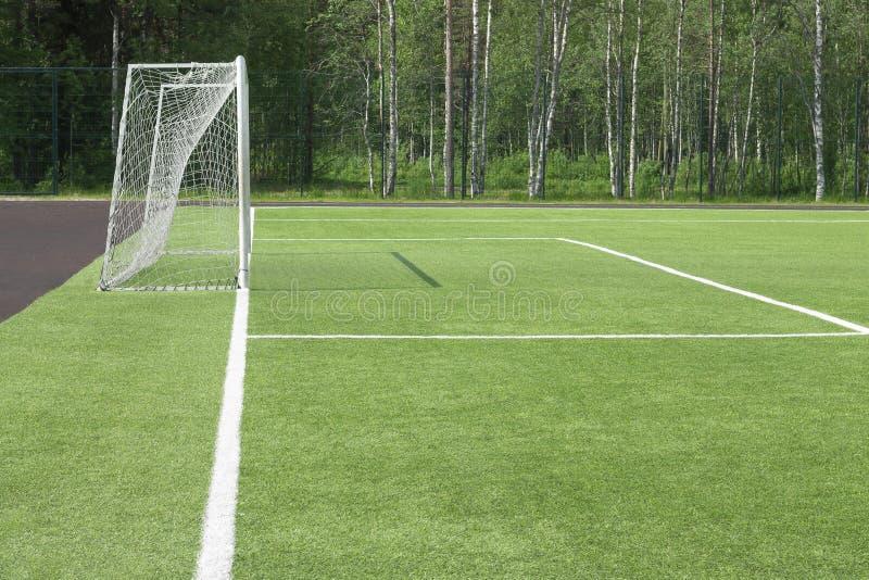 Fotbollmål i fältet Från vilket skuggan på ett grönt gräs faller En blick med en sida arkivfoto
