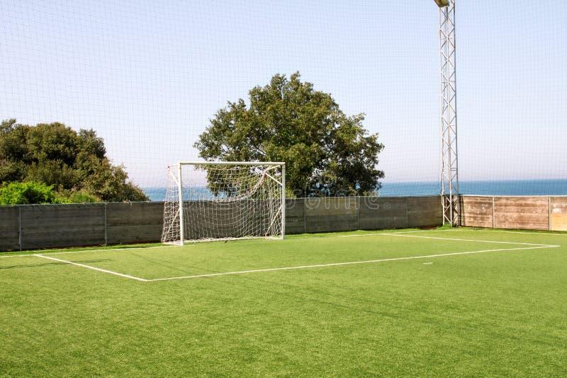 Fotbollmåldörren med vit förtjänar Fotbollmål på fotbollfältet med grönt gräs och sportstadion på universitetsområdet, vit linje arkivfoto