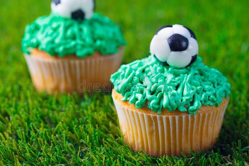 Fotbollparti, födelsedag dekorerad muffin på bakgrund för grönt gräs close upp royaltyfri bild