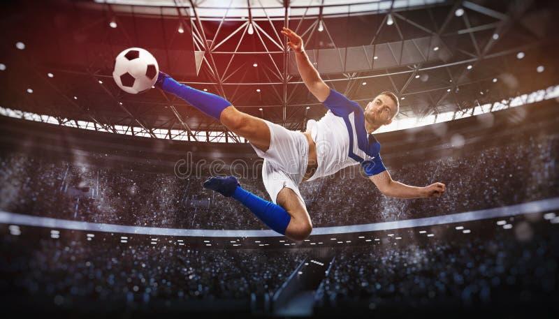 Fotbollplats p? nattmatchen med spelaren som sparkar bollen med makt arkivbilder