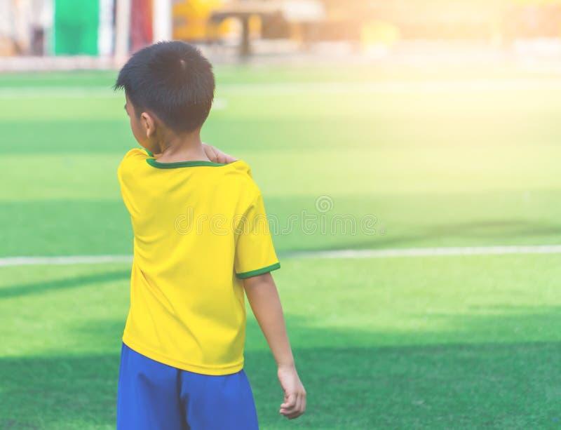 Fotbollpojke som bara står på utbildningsjordning arkivbild