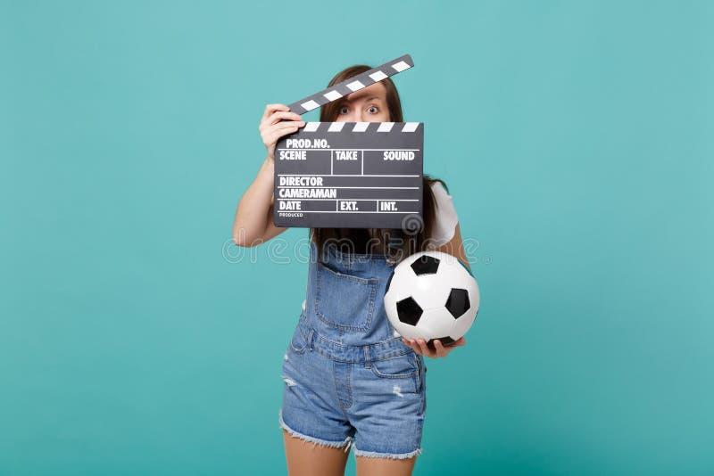 Fotbollsfan för ung kvinna med fotbollbollen som täcker den isolerade framsidan med den klassiska svarta filmen som gör clapperbo royaltyfria bilder