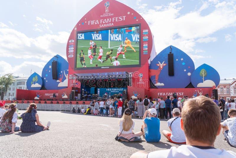 Fotbollsfan håller ögonen på levande TV-sändning av matchen i fanzon arkivbilder