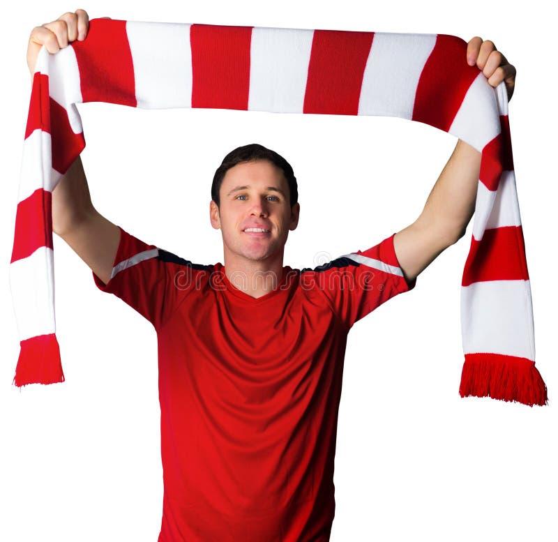 Fotbollsfan i röd hållande halsduk arkivbilder