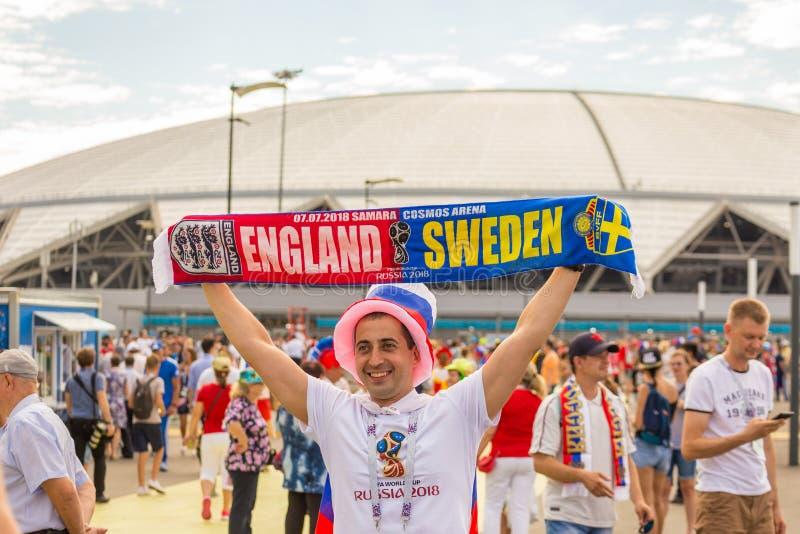 fotbollsfan visar flaggan av fotbollleken England Sverige mot bakgrunden av stadion på världsmästerskapen royaltyfri foto