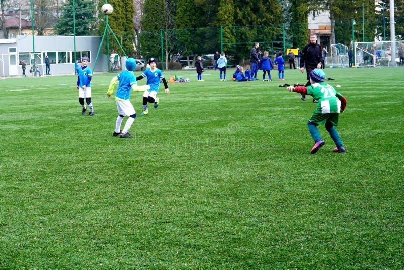 Fotbollslag f?r barn` s p? graden Barns jordning f?r fotbollutbildning Unga fotbollspelare som jagar bollen arkivfoton