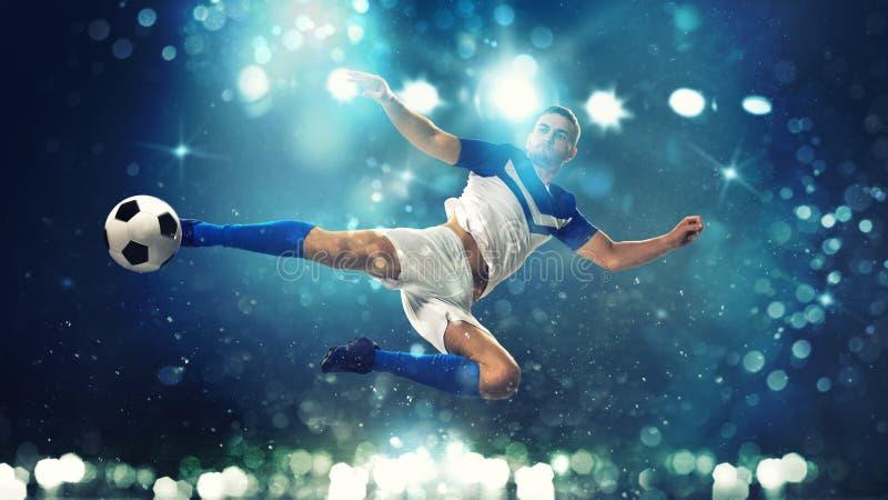 Fotbollslagmannen slår bollen med ett akrobatiskt sparkar in luften på mörkt - blå bakgrund arkivbild