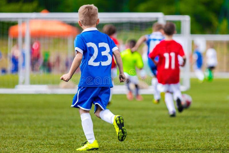 Fotbollspark; Rinnande fotbollfotbollsspelare Junior Soccer League fotografering för bildbyråer