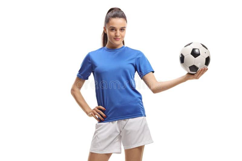 Fotbollspelare för ung kvinna som rymmer en fotboll arkivfoto