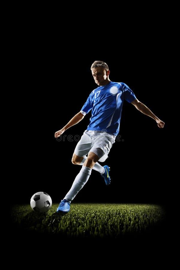 Fotbollspelare för yrkesmässig fotboll i handling som isoleras på svart fotografering för bildbyråer