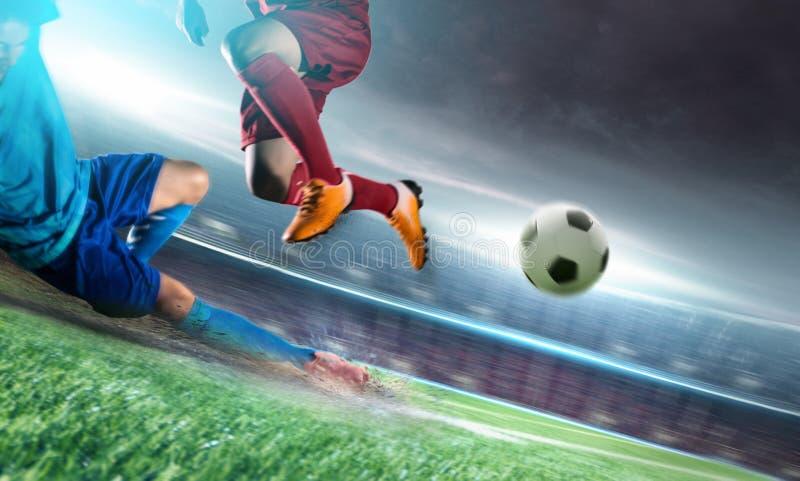 Fotbollspelare i handlingsparkboll på stadion royaltyfri fotografi