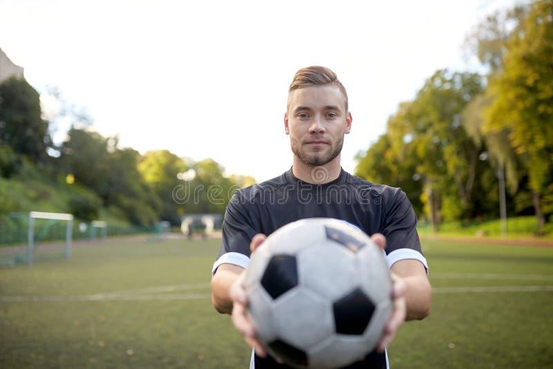 Fotbollspelare med bollen på fotbollfält arkivbild