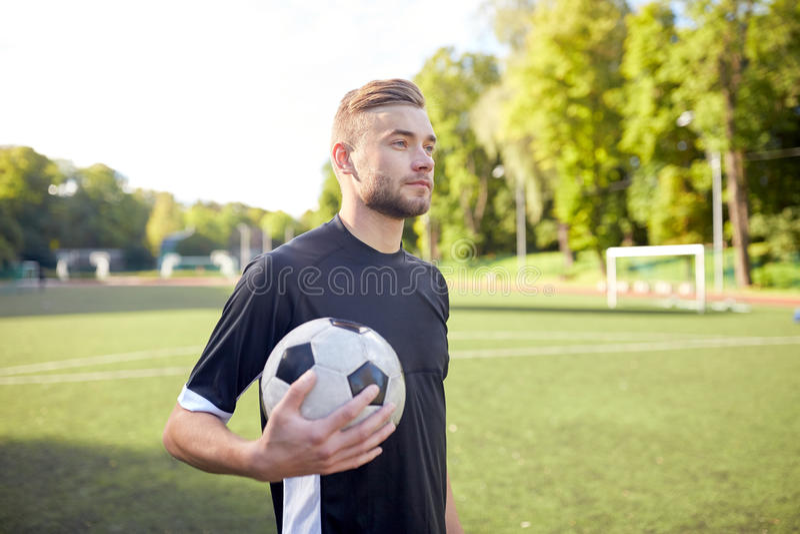 Fotbollspelare med bollen på fotbollfält royaltyfri fotografi