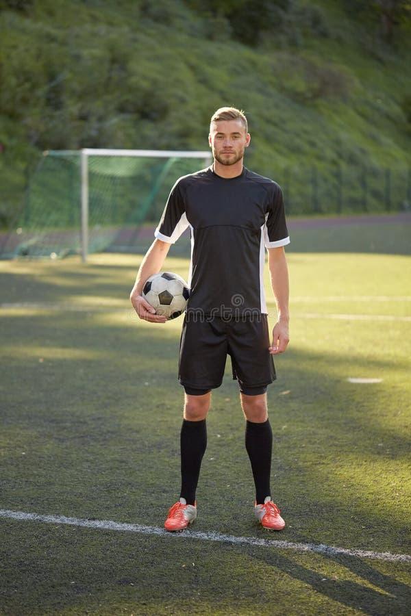 Fotbollspelare med bollen på fotbollfält arkivbilder