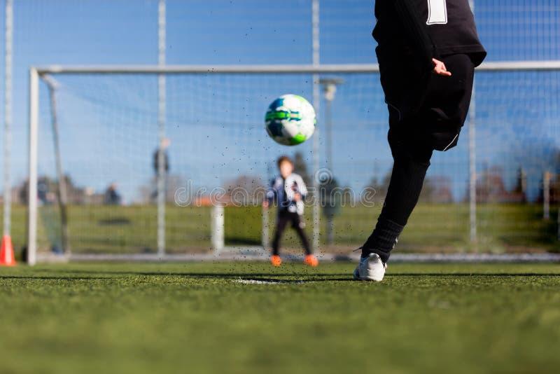 Fotbollspelare och goalie under straffshootout royaltyfri fotografi
