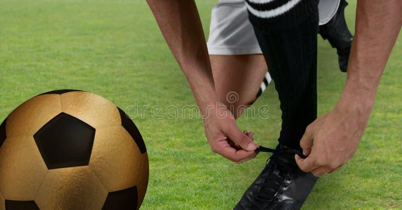 fotbollspelare som binder hans skor med den guld- bollen royaltyfri illustrationer