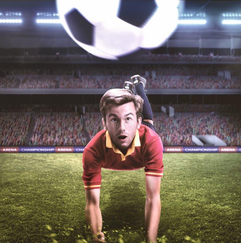 Fotbollspelare som hoppar för en titelrad på fotballfält royaltyfria bilder