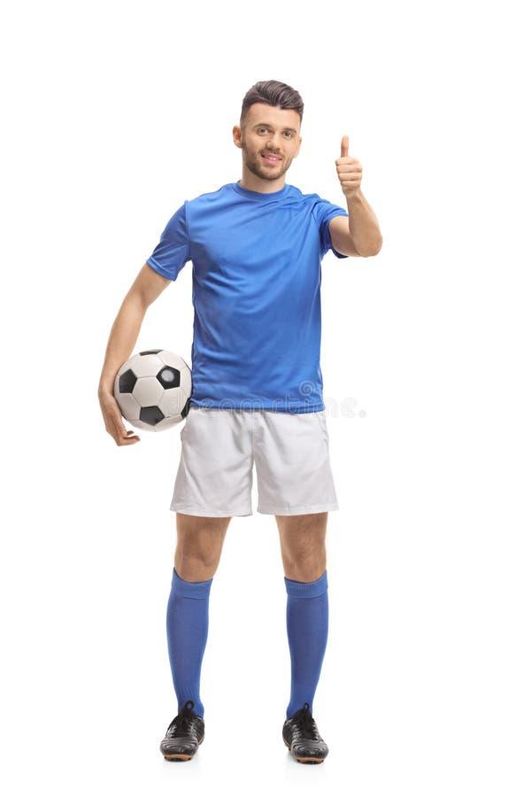 Fotbollspelare som rymmer en fotboll och gör en tumme upp tecken royaltyfri fotografi