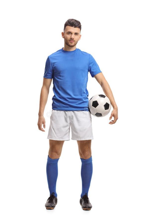 Fotbollspelare som rymmer en fotboll och ser kameran royaltyfria foton