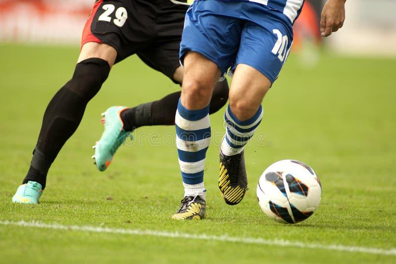 Fotbollspelare som skyddar en boll fotografering för bildbyråer