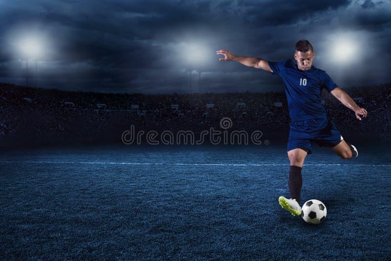Fotbollspelare som sparkar bollen i en stor stadion på natten royaltyfri fotografi